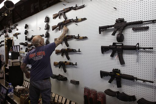 Mel Bernstein takes down an AK-47 assault rifle from a sales rack at his Dragonman's gun store, east of Colorado Springs, Colo. Federal law requires background checks on gun sales in stores like Bernstein's but exempts private sales. Efforts to expand background checks have foundered in Washington, but Maine legislators now have a chance to make up for the impasse at the federal level.