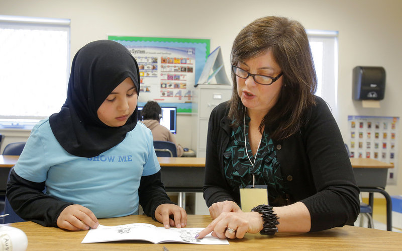 Lisa DeSisto, publisher and CEO of the Portland Press Herald/Maine Sunday Telegram, listens to East End Community School third-grader Lana Al Rubaye read Friday in Portland. DeSisto was visiting via the Principal for a Day program.