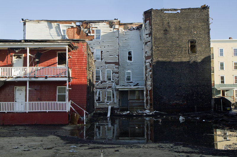 Buildings stand in the aftermath of a massive fire at Bartlett and Pierce streets in Lewiston. Firefighters poured so much water onto the roofs of both buildings on Pierce Street that torrents of water cascaded out windows and doors and into the streets.