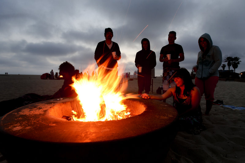 Blazing fire pits like this one on Huntington Beach, Calif., have ignited controversy over their possible contribution to air pollution. Air quality regulators are considering a proposal to ban beach bonfires in Southern California.