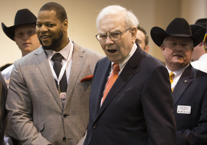 Warren Buffett and Detroit Lions Defensive tackle Ndamukong Suh react as Buffett misses a putt at the Justin Boots booth Saturday. Justin Boots, a Berkshire subsidiary, was promoting its new line of golf shoes.