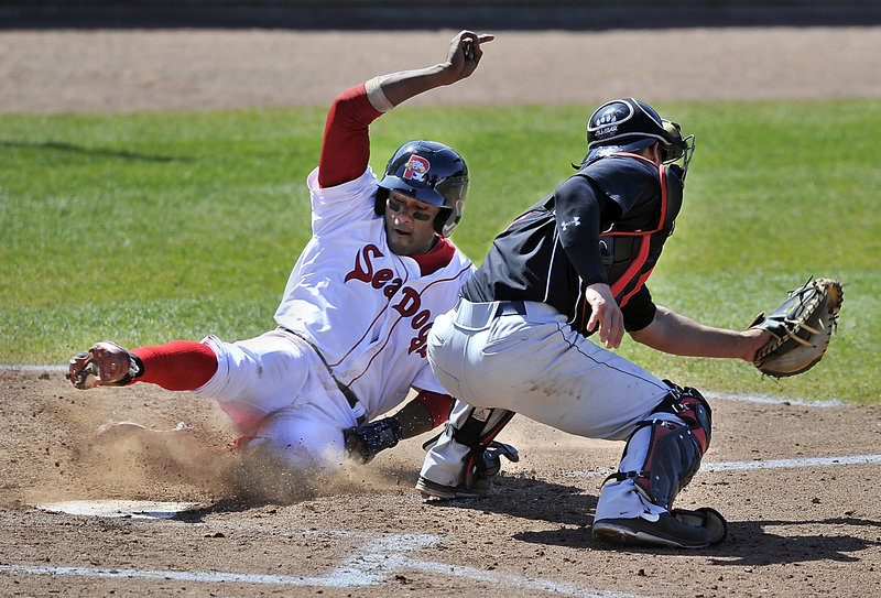 Portland's Tony Thomas slides around catcher Dan Rohlfing to tie the game at 1-1 after leading off the seventh inning with a double during Saturday's 2-1 victory.