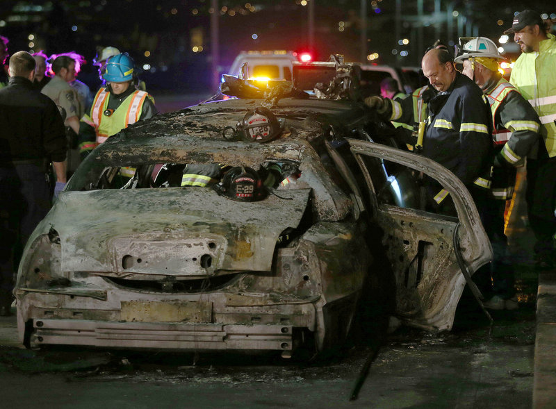 Officials investigate the scene of a limousine fire on the westbound side of the San Mateo-Hayward Bridge in Foster City, Calif., on Saturday night. Five people died when they were trapped in the limo; four others and the driver escaped.