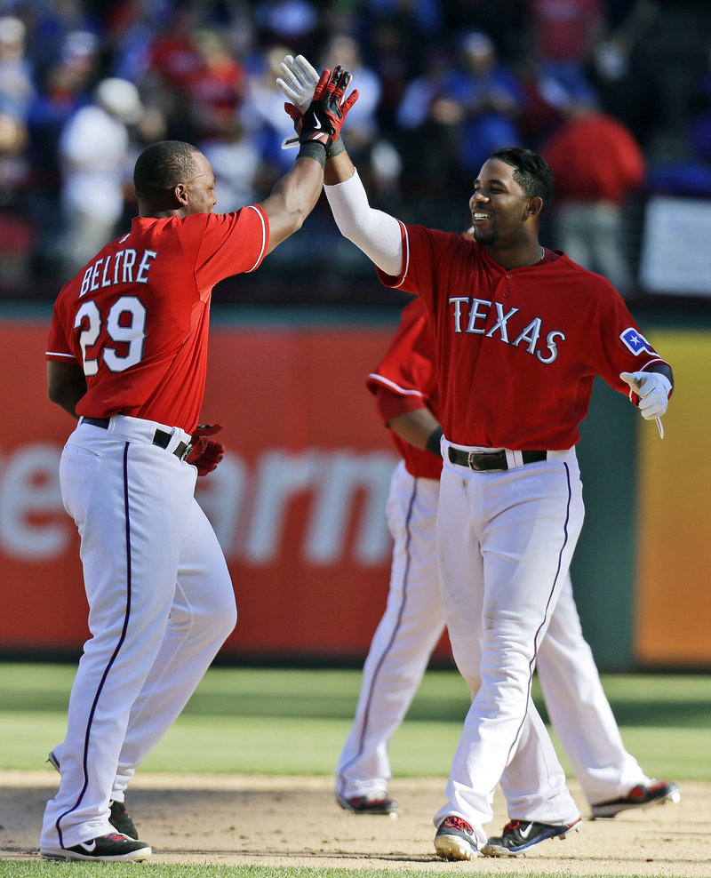 The Rangers' Adrian Beltre, left, celebrates with Elvis Andrus after Beltre delivered a winning RBI single in the bottom of the ninth inning in a 4-3 win against the Red Sox at Arlington, Texas on Sunday.