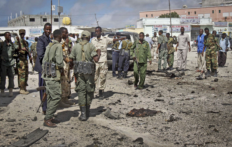 Somali soldiers gather at the scene of a suicide car bombing in Mogadishu on Sunday. Police said the bomber tried to ram a car laden with explosives into a military convoy.