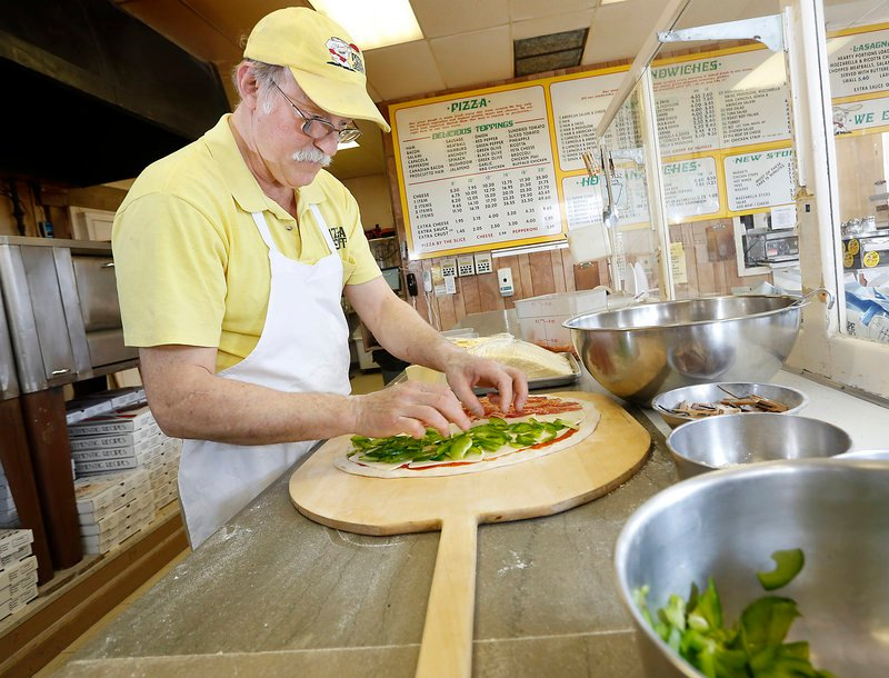 Joe Poliquin creates a pie at the Pizza Joint in South Portland.