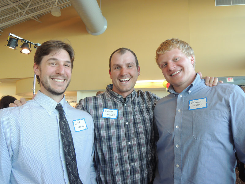 Auction volunteers Erik Lema, Tyler Gaudet and Phillip Szela, all of Portland, man the For Him tables at the fundraiser.