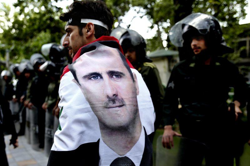 A Syrian man wrapped in a Syrian flag bearing the portrait of President Bashar Assad walks past anti-riot police during an anti-Israeli demonstration in front of the United Nations office in Tehran, Iran, on Monday.