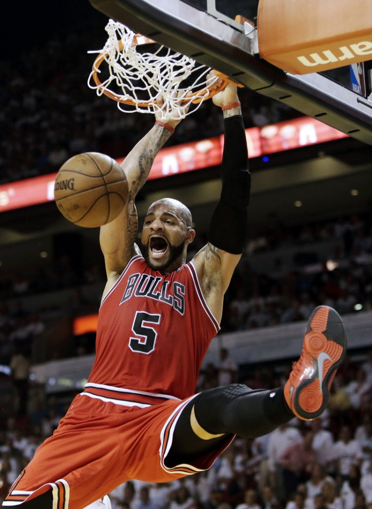 Bulls forward Carlos Boozer throws down an emphatic dunk during Chicago's 93-86 upset win over the Heat in their playoff opener at Miami on Monday.