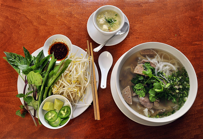 Saigon serves its beef pho with a plate of fresh basil, bean sprouts, lime and jalapeno pepper slices, and hot oil. It comes with a small bowl of tofu soup, top, as a starter. In the pho pictured are beef broth, noodles, onion, Asian cilantro and four kinds of meat.