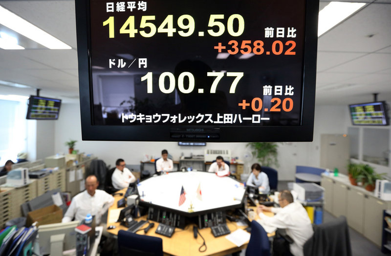 Dealers in Tokyo work under a monitor displaying a figure of the Nikkei 225 Stock Average, top, and the exchange rate of the yen against the U.S. dollar.