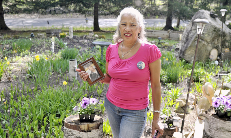 """Ramona Torres of Denmark holds a photo of her son who disappeared 14 years ago, as she stands by the garden she made as a memorial to his life. """"I go there and I talk to him when something happens to us,"""" she said."""