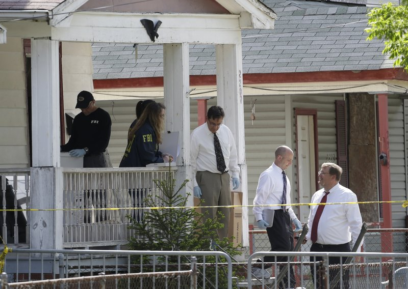 Law enforcement officials gather evidence Thursday at the crime scene in Cleveland, Ohio, where three women and a child were held captive. Former school bus driver Ariel Castro, 52, is being held on $8 million bail, charged with rape and kidnapping.