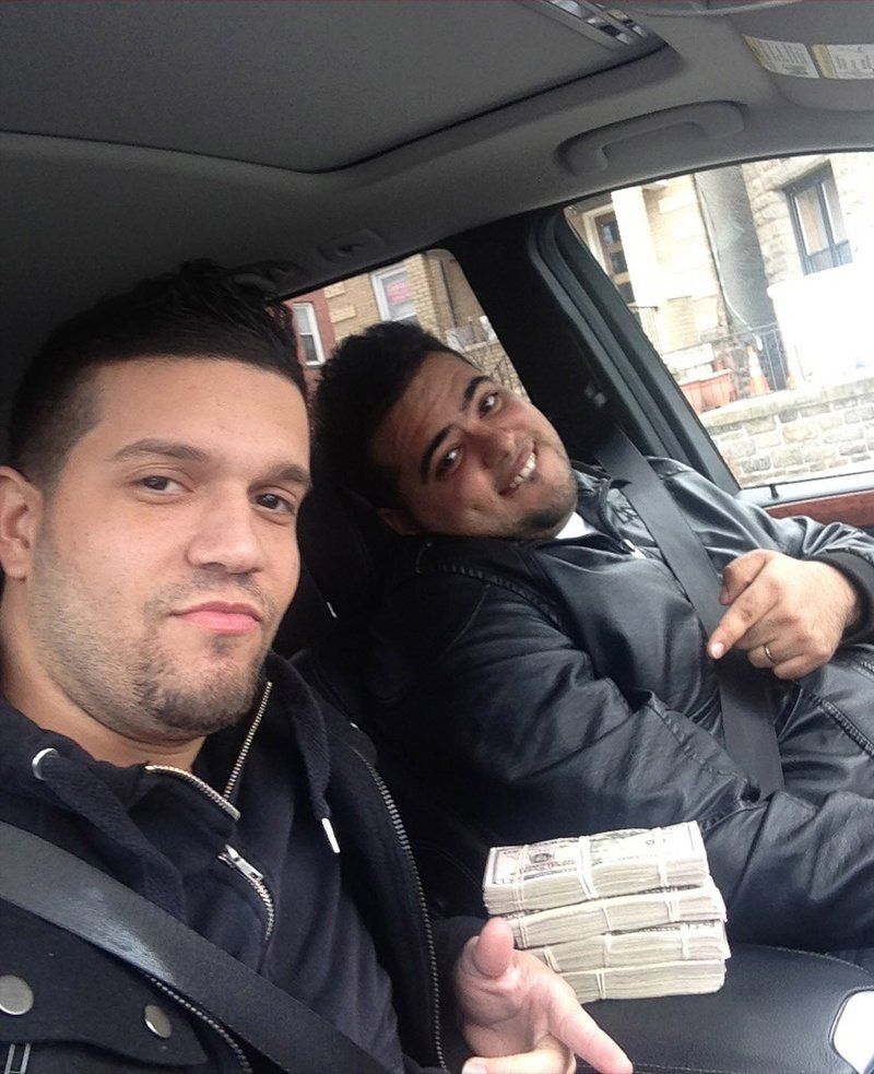 Elvis Rafael Rodriguez, left, and Emir Yasser Yeje pose with bundles of cash allegedly stolen using bogus magnetic swipe cards at cash machines throughout New York, prosecutors say. Prosecutors say they are members of worldwide gang of criminals who stole $45 million in hours by hacking into a database of prepaid debit cards.