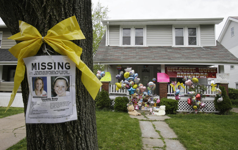 A poster and bow are still tied to a tree outside the Cleveland home of Amanda Berry, where a welcome sign and balloons decorate the porch.