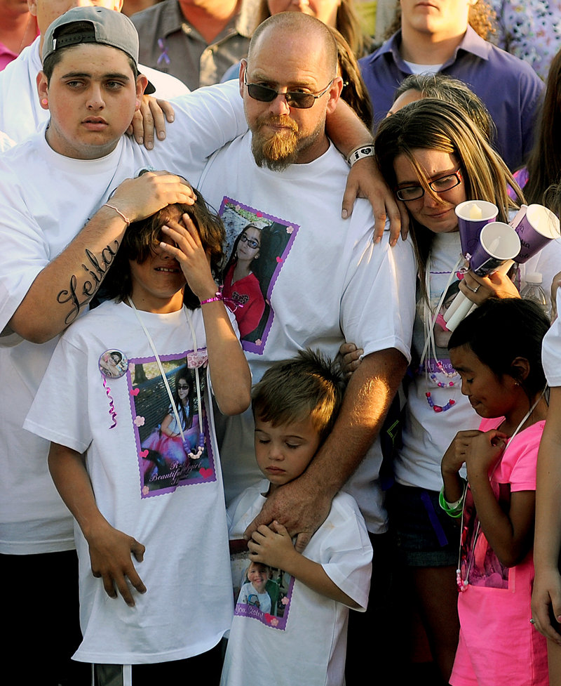 The family of 8-year-old Leila Fowler attends a vigil for her April 30 in Valley Springs, Calif. Her father, Barney Fowler, center, stands with her stepmother, Crystal Walters, right.
