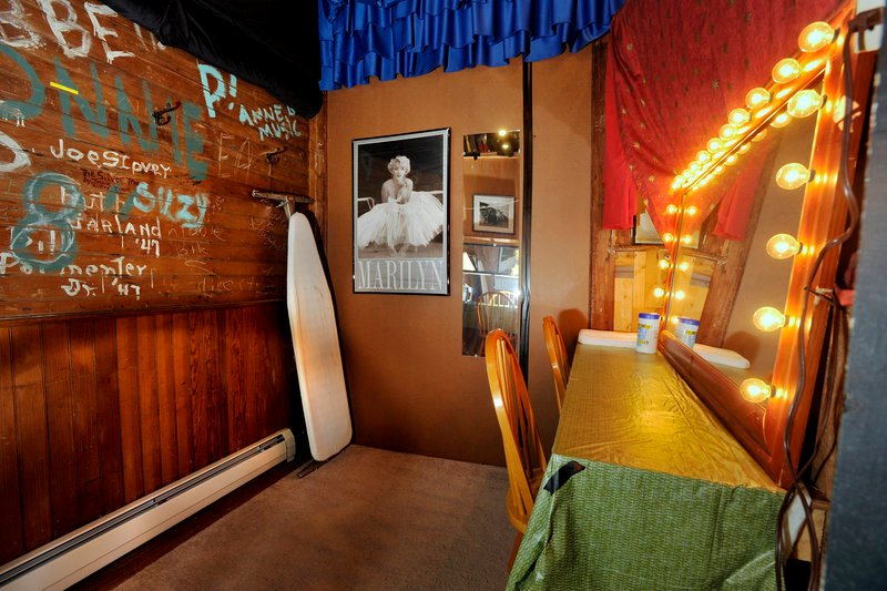 The backstage dressing room's walls are signed by those who have entertained audiences in the past, and an ironing board stands at the ready for use by current performers.