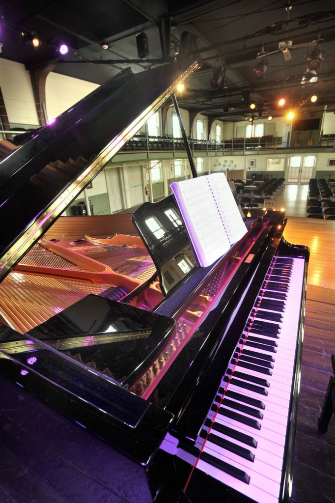 A grand piano graces the opera house stage.