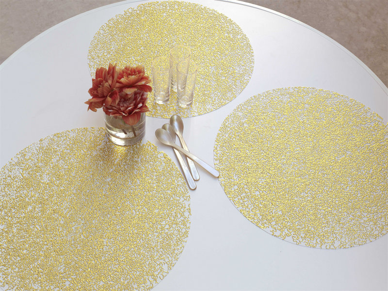 Pressed filigree gold-white placemats by Sandy Chilewich are spot printed with metallic foil to suggest the weathered look of a delicate old textile.