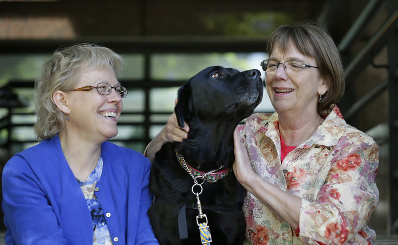 Courthouse dog Molly B sits with Ellen O'Neill-Stephens, right, a former prosecutor in Seattle who founded the Courthouse Dogs Foundation, and Celeste Walsen, left, the organization's executive director.