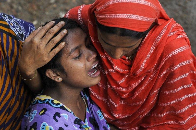 A woman cries last week after identifying the body of her father at a makeshift morgue near the site of a Bangladesh clothing factory's April 24 collapse. American companies' participation is critical to the success of an accord committing clothing retailers to hiring safety inspectors for and upgrading their factories in Bangladesh.
