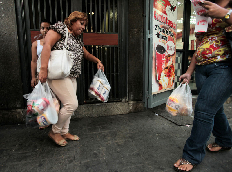A customer leaves a supermarket in Caracas on Wednesday. Venezuela says it will import 50 million rolls of toilet paper to boost supplies.