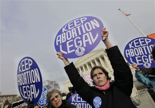 Abortion-rights activists hold up signs as anti-abortion demonstrators march toward the Supreme Court in Washington on Jan. 22, 2010, the 37th anniversary of the high court ruling that decriminalized abortion. Bills such as those now before the Maine Legislature are part of a push by opponents of abortion to chip away at women's reproductive rights.