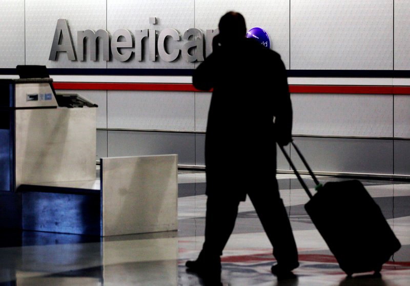 A passenger with a rolling suitcase walks through an American Airlines baggage claim area at O'Hare International Airport in Chicago in 2011.