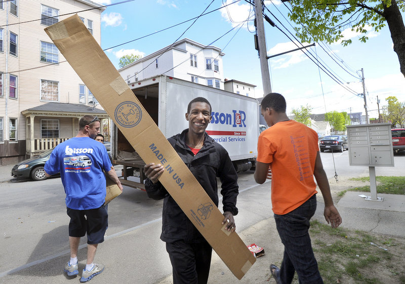 Mohamed Mohamed, 17, smiles as he carries a bed frame into the apartment building.