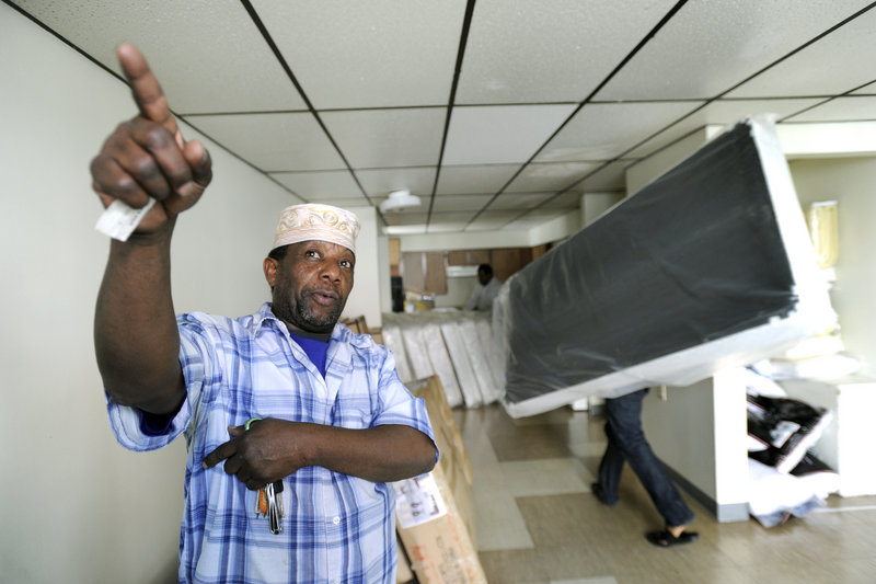 Displaced Lewiston fire victims get bedding, beds and furniture delivered to their new apartments Friday. Above, Ali Sheikh directs his family's move into a new apartment at 49 Knox St. in Lewiston.
