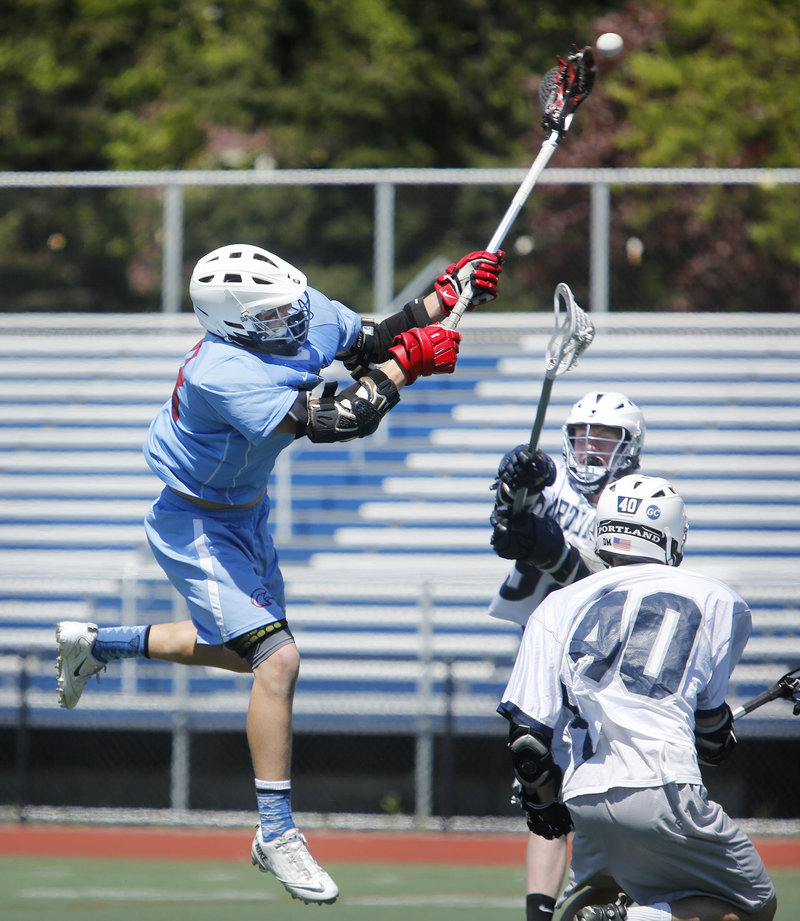 Griffin Jacobson of Windham unleashes a shot over Portland defenders Spencer Cohen (40) and Charlie Kovarik.