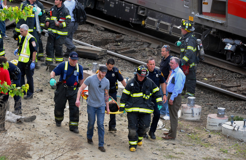 Rescuers transport an injured passenger from the scene where two Metro North commuter trains collided Friday. The accident snarled train traffic from New York to Boston.