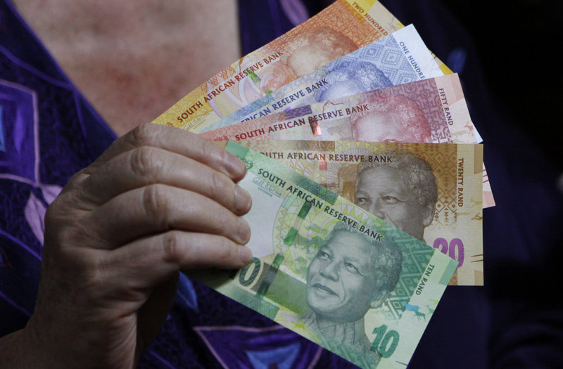 Banknotes bearing Mandela's image are displayed last year in Pretoria. Across the country Mandela's face is a familiar sight, beaming from T-shirts, drink coasters and the new banknotes.