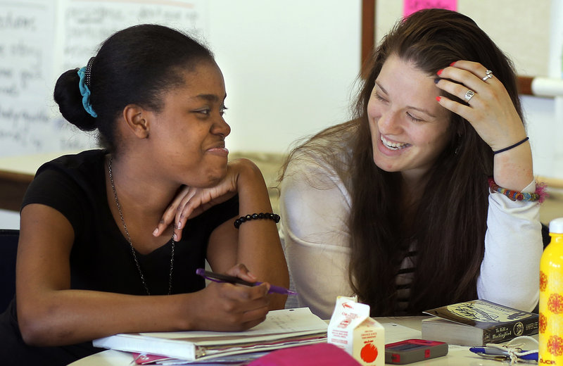 Dejaunie Madourie, 14, a Portland High freshman, shares a laugh with AmeriCorps worker Erica Small, at right, while working together on English homework last week as part of Make It Happen! The program gives academic coaching, encouragement and college application help to students who learned English as a second language. Society benefits when students like Dejaunie gain access to higher education through programs like Make It Happen!