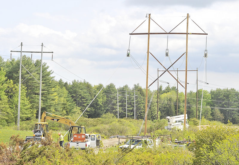 Hawkeye crew members adjust the tension on newly installed utility poles and wires near Smutty Lane in Saco on Monday, May 20, 2013.