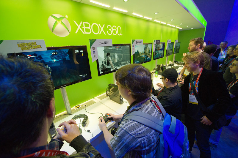 Attendees play with Microsoft's Xbox 360 game console at the Consumer Electronics Show in Las Vegas. Microsoft faces threats from companies including Apple and Facebook.