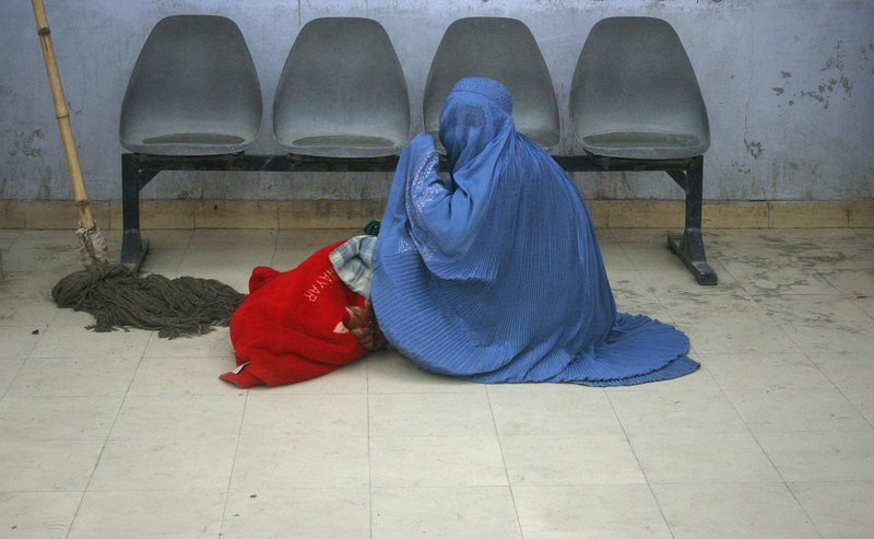 "An Afghan woman awaits help in a clinic. Despite reforms to improve women's rights, the rate of imprisonment of women and girls for ""moral crimes"" has increased 50 percent."