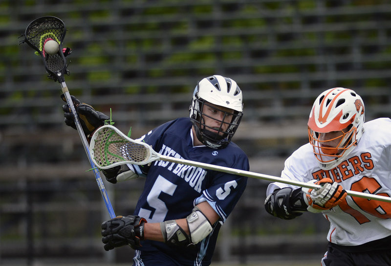 Ben Grant of Westbrook High drives the ball down the field Wednesday as Callum Maloy of Biddeford moves in to defend during their SMAA schoolboy lacrosse game at Biddeford.