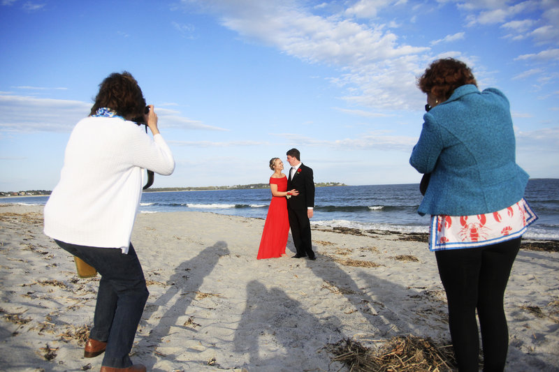 Mackenzie Leighton, a junior at Cape Elizabeth High School, and Connor Maguire, a senior, pose on the beach as they are photographed before the prom by their mothers, Gwyneth Maguire, left, and Susan Leighton, right, May 18. After the dance, the couples returned to a Pine Point cottage to eat the leftovers from the potluck, make s'mores and play guitar by a fire pit.
