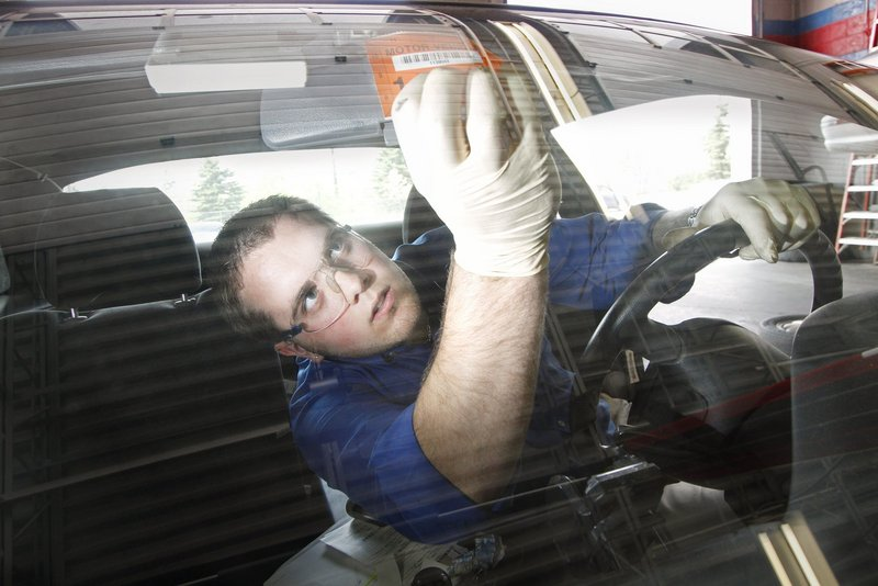 "Erik Lowell of AAA Car Care in Portland puts a new sticker on a car after he inspected and passed the vehicle in 2011. A reader says Maine's car inspection mandate amounts to ""a regressive tax."""