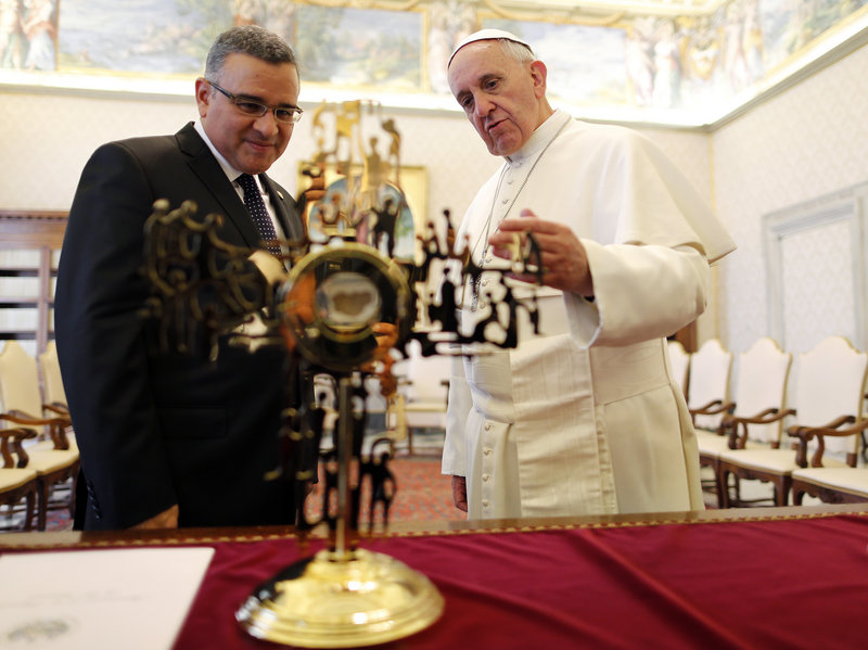 During a private audience at the Vatican on Thursday, Pope Francis speaks with El Salvador's President Mauricio Funes as they stand in front of a reliquary containing a fragment of the vestment that archbishop Oscar Romero was wearing when he was assassinated.
