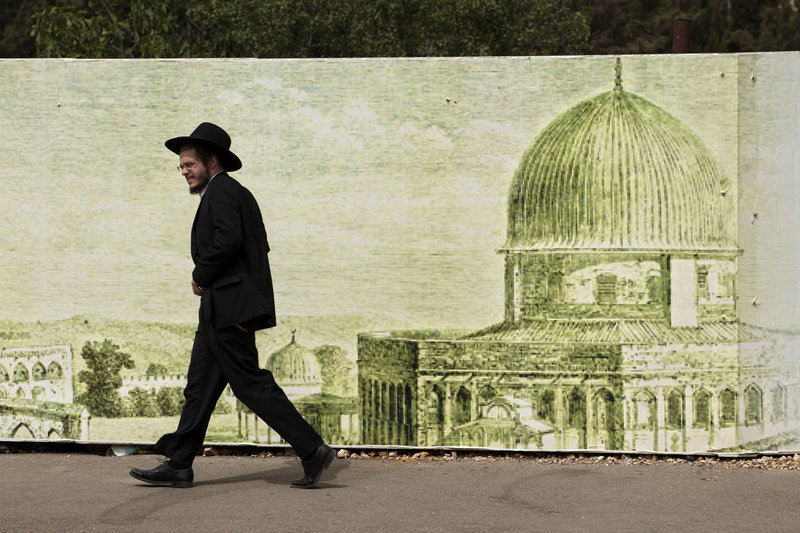 Ultra-Orthodox Jews, like this man walking past a sign depicting the Dome of the Rock Mosque in Jerusalem, are among the most vocal opponents of a plan that would gradually limit what have been automatic exemptions from military service.
