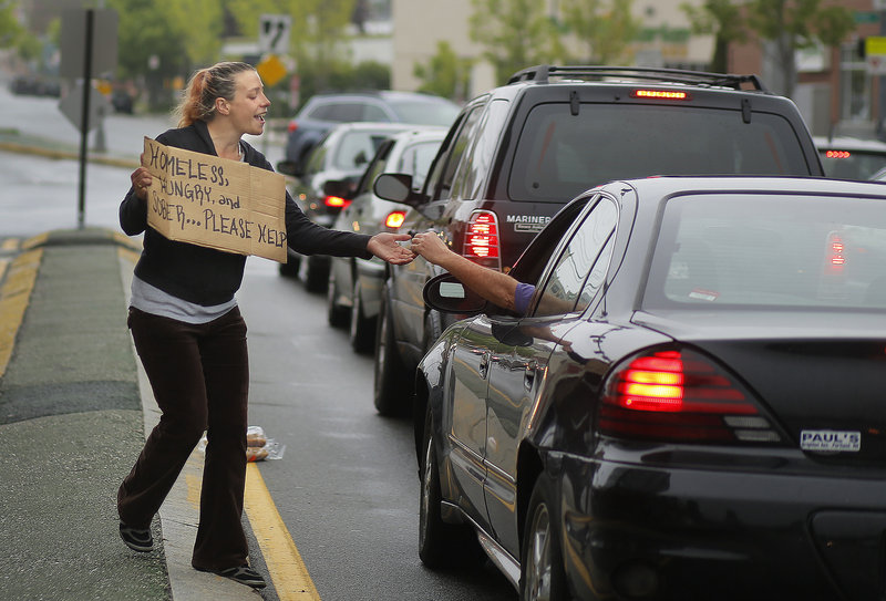 Alison Prior, 29, of Portland, receives change from a passerby while she panhandles at the corner of Preble Street and Marginal Way on Friday, May 24, 2013. Prior says she panhandles for extra money while she and her boyfriend look for an apartment.