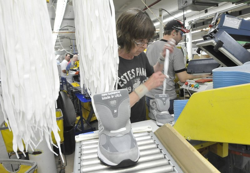 Sharon Estes laces shoes at New Balance's Norridgewock factory. The company employs roughly 900 people in factories in Norridgewock, Skowhegan and Norway, Maine.