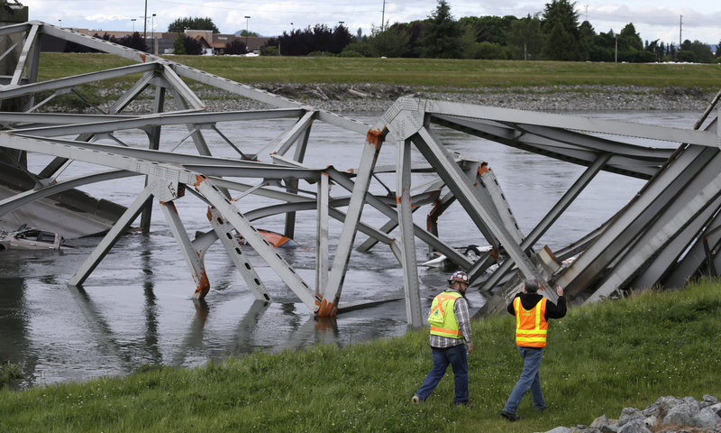 Workers walk past the collapsed Interstate 5 bridge in Mount Vernon, Wash., on Friday