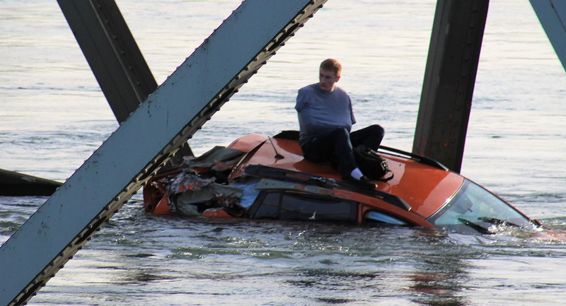 A man, at left, awaits rescue atop a car that fell into the Skagit River, in a photo provided by Francisco Rodriguez.