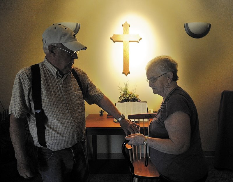 "Gerald ""Jake"" Ellis, 79, reaches for the hand of his wife, Pauline Ellis, 79, in the chapel at Lakewood Nursing Home in Waterville Wednesday. A resident of the home's dementia ward, Pauline Ellis has enjoyed improved quality of life after being taken off antipsychotic drugs."