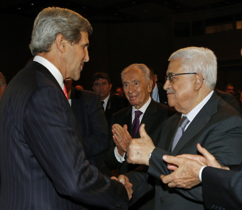 John Kerry shakes hands with Palestinian President Mahmoud Abbas, right, while Israeli President Shimon Peres, center, observes at the World Economic Forum on the Middle East and North Africa in Jordan on Sunday.