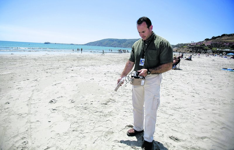 Scott Milner of the San Luis Obispo County Department of Environmental Health uses a radiation measuring device to check Avila Beach in California for any dangerous debris.