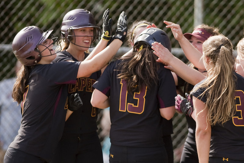 Ashley Tinsman receives pats from her Cape Elizabeth teammates Thursday after hitting a solo home run in the third inning of the 5-0 victory against Greely.